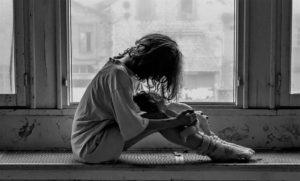 vrouw zit eenzaam op de grond met een pop