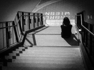 vrouw zit eenzaam op trap