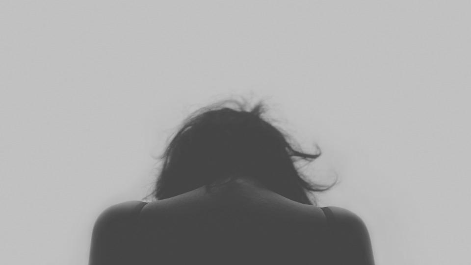depressieve vrouw buigt haar hoofd voorover