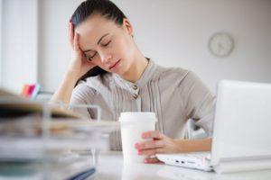 vermoeide vrouw zit achter bureau
