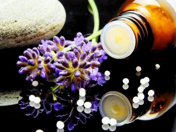 flesje met globuli (korrels) en twee paarse bloemen