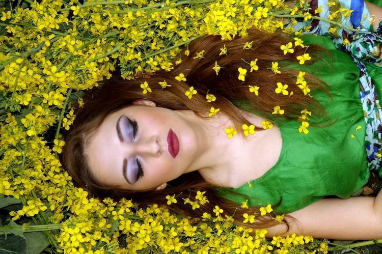 vrouw ligt op de grond tussen bloemen te dromen