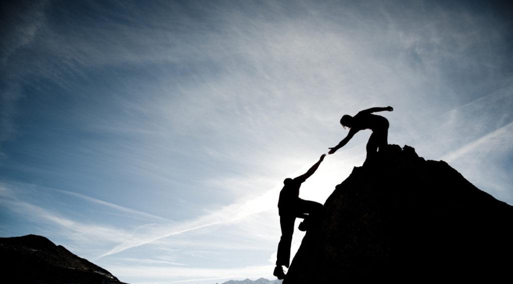 vrouw helpt iemand om berg op te klimmen