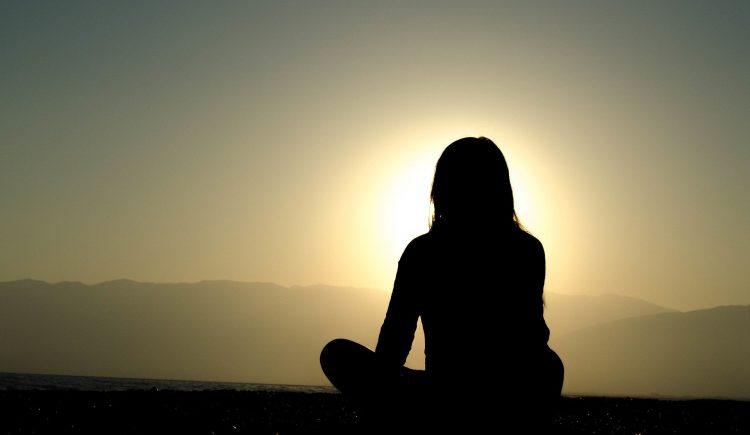 vrouw is aan het mediteren tijdens zonsondergang