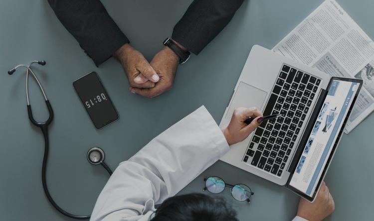 dokter legt aan patiënt iets uit aan de hand van laptop
