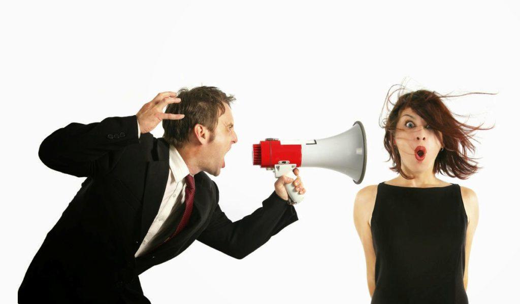 kritiek wordt gegeven door een man door een luidspreker aan een vrouw