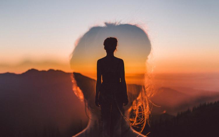 vrouw kijkt uit op zon, een hoofd van een tweede vrouw kijkt mee