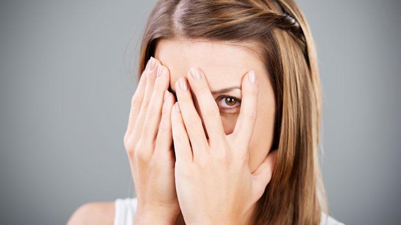 verlegen vrouw verbergt achter handen haar gezicht
