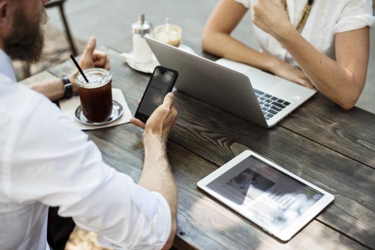 man kijkt op mobiele telefoon, tablet ligt op tafel, iemand anders zit achter laptop