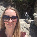 Femke de Grijs staat voor een pinguïn in Zuid-Afrika