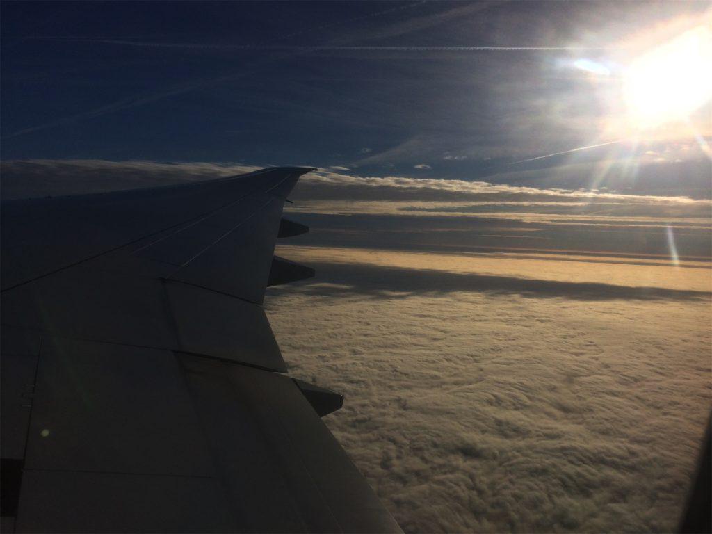 vliegtuig vleugel met zon en wolken
