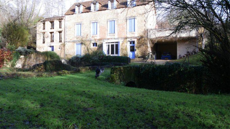 Schapendoes Otje rent in de tuin voor een huis in de Dordogne
