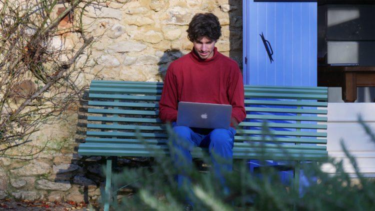 Mathijs van der Beek zit op een bankje in de Dordogne