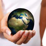 vrouw houdt in hand een wereldbol vast