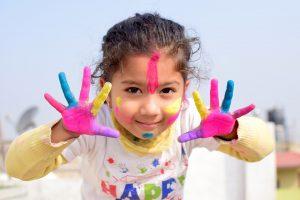 kind heeft verf op gezicht en handen
