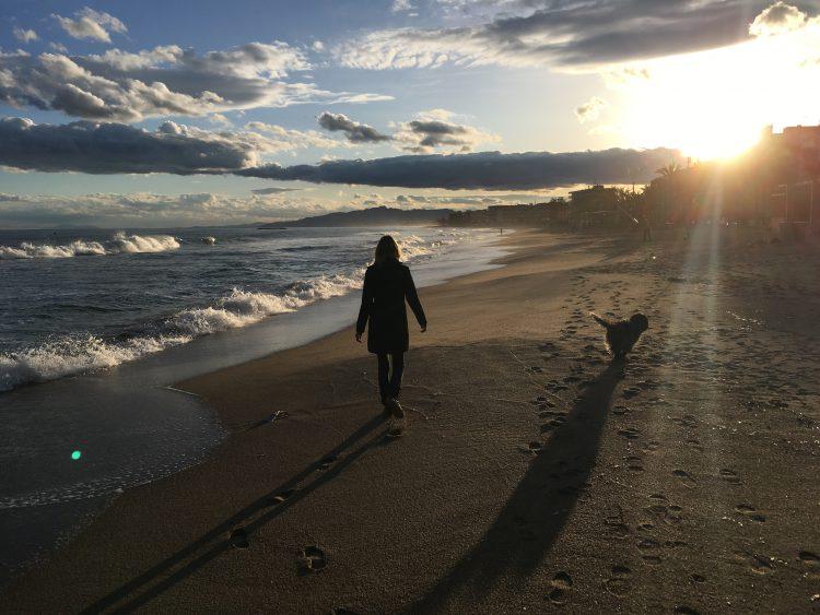 Femke de Grijs loopt op strand in Salou met Schapendoes Otje