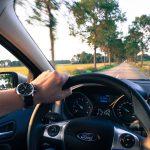 een arm en hand die een stuur van het merk Ford vasthoudt en kijkt naar de weg