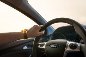 een hand die een stuur van het merk Ford vasthoudt