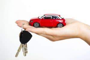 rode speelgoedauto in hand van vrouw met sleutelbos aan ringvinger