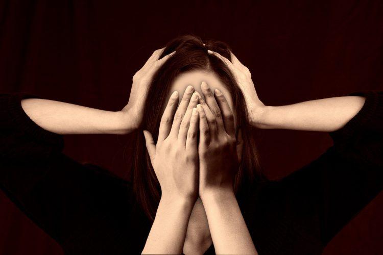 onzekere vrouw verbergt gezicht achter handen